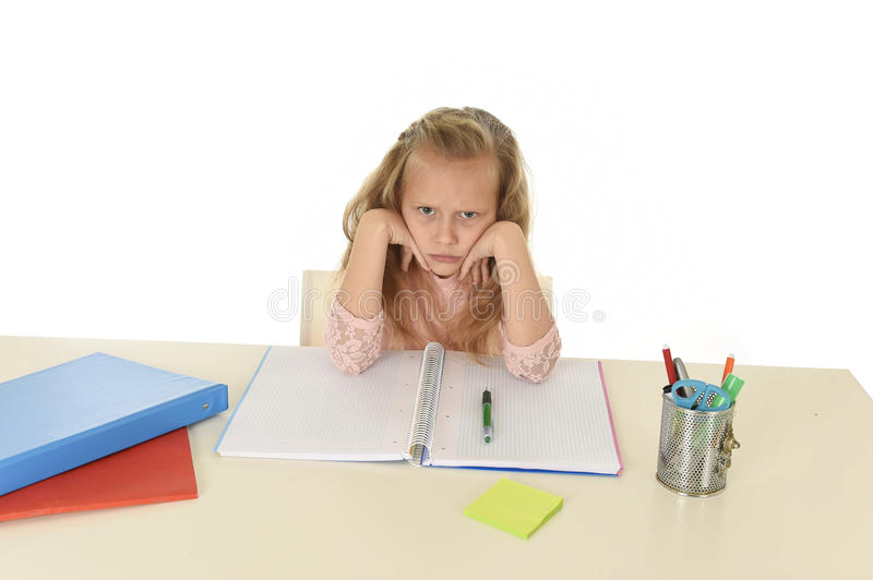 Little schoolgirl sad and tired looking depressed suffering stress overwhelmed by load of homework. Sweet little schoolgirl sad and tired looking depressed royalty free stock image