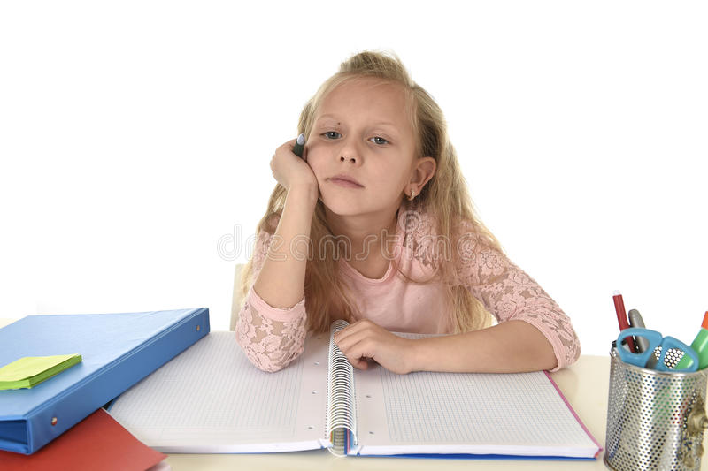 Little schoolgirl sad and tired looking depressed suffering stress overwhelmed by load of homework. Sweet little schoolgirl sad and tired looking depressed royalty free stock photo