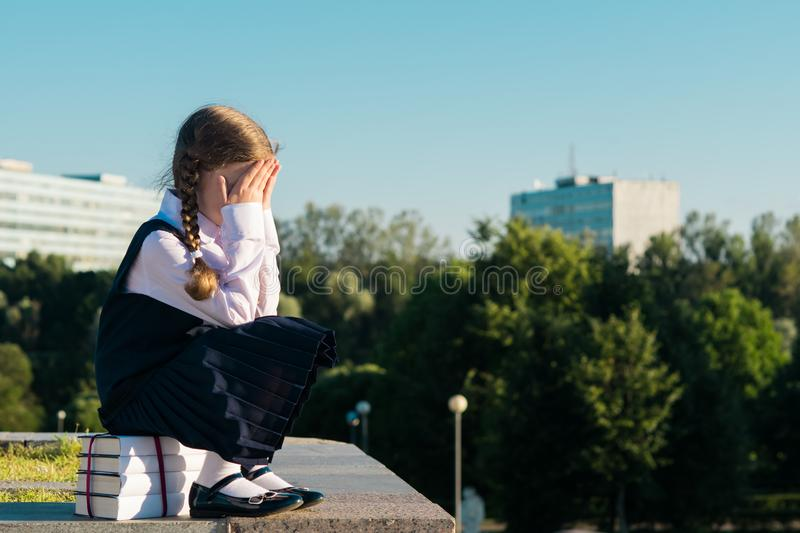 Little schoolgirl sits on a textbook and cries, does not want to study stock image