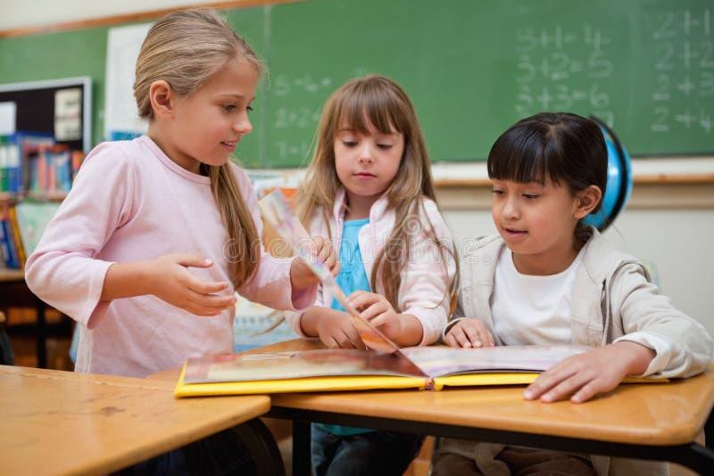 Little Schoolgirls Reading A Fairy Tale Royalty Free Stock Photos
