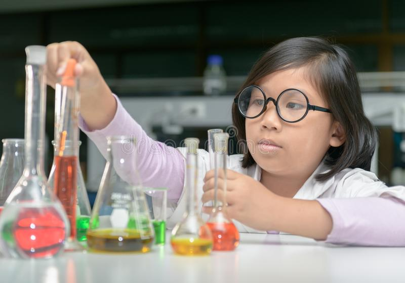 Little scientist in lab coat making experiment stock photo