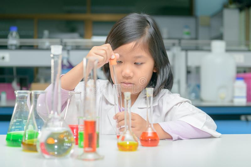 Little scientist in lab coat making experiment stock image