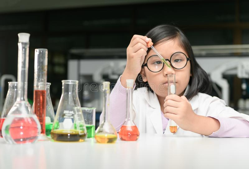 Little scientist in lab coat making experiment stock photography