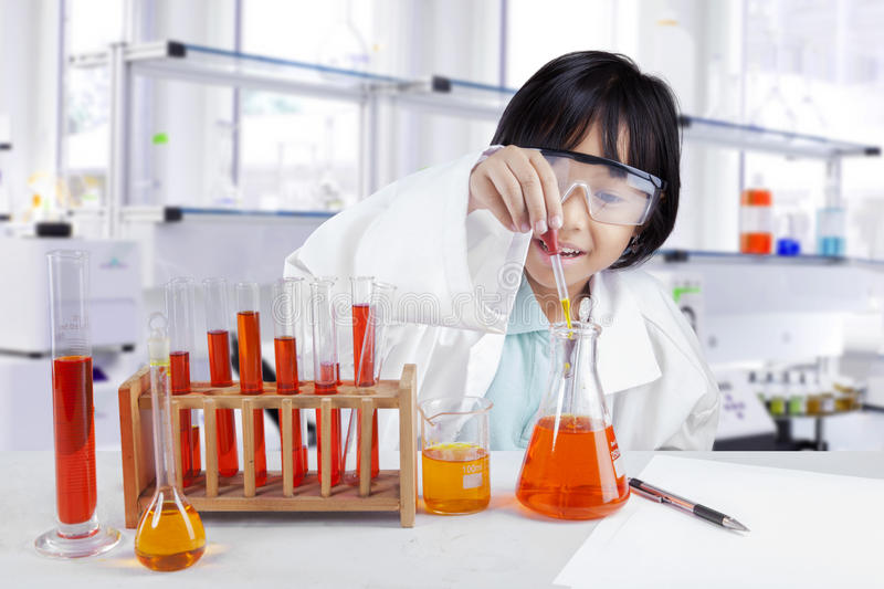 Little scientist making chemical research royalty free stock image