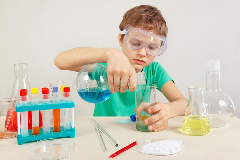 Little scientist in safety goggles doing chemical experiments in laboratory. Little scientist in safety goggles doing chemical experiments in the laboratory royalty free stock photography