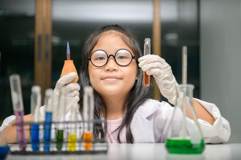 Little scientist use dropper to making experiment in chemical laboratory stock photography