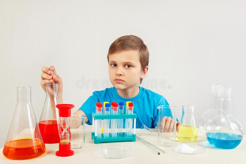 Little serious boy doing chemical experiments in laboratory. Little serious boy doing chemical experiments in the laboratory stock image
