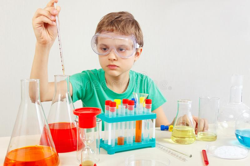 Little serious boy in safety glasses doing chemical experiments in laboratory. Little serious boy in safety glasses doing chemical experiments in the laboratory royalty free stock photography