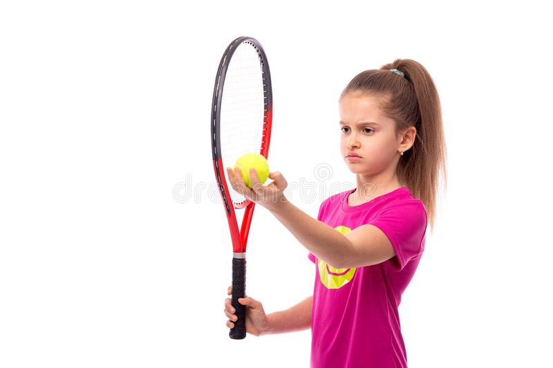 A  serious girl wearing  pink T-shirt stands with a tennis racket and  ball  and focuses on the cast, isolated. A little serious girl wearing  pink T-shirt royalty free stock images
