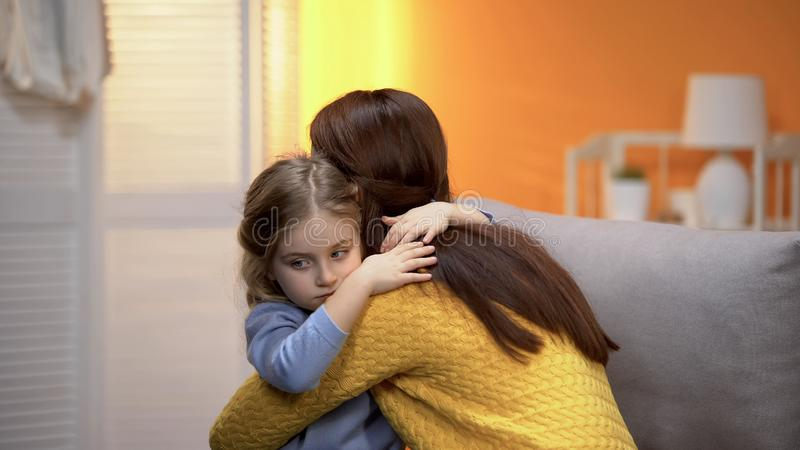 Little shy adopted girl hugging young female, beginning of new life in family stock photography