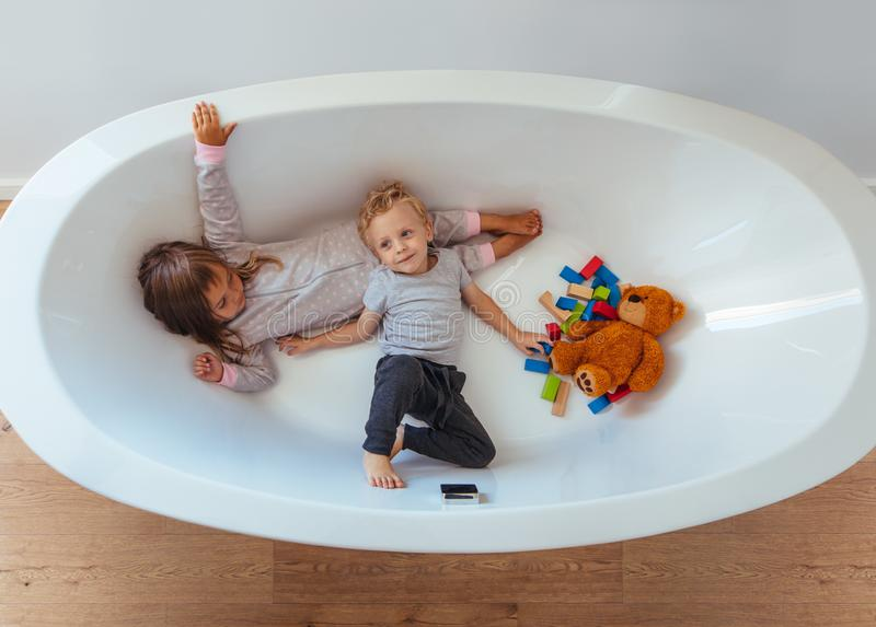 Little siblings playing inside a bathtub royalty free stock image
