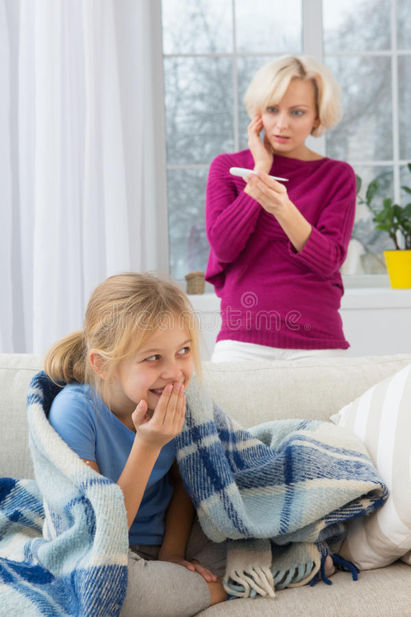 Little sick girl under blanket smiling, concerned mom on background. stock photo
