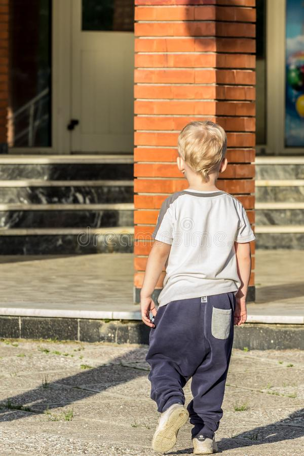A little single boy walking in the yard, back side view. Friendship of school boys. royalty free stock photography