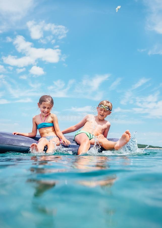 Little sister and brother sit on inflatable mattress in the sea. Happy summer holidays concept image stock photo