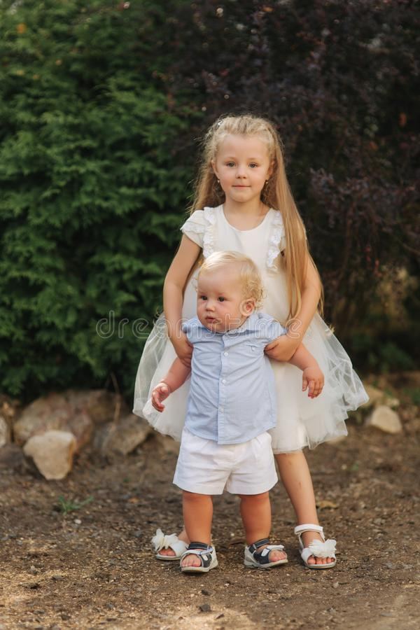 Little sister and brother walkind outside. Beautiful children in summer time. Blond hair chidren stock images