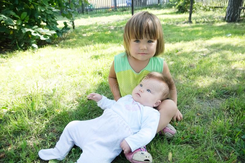 Little sisters in the backyard. Smiling kids sitting on grass in summer. Children in family: toddler and baby portrait. Happy childhood concept stock photography