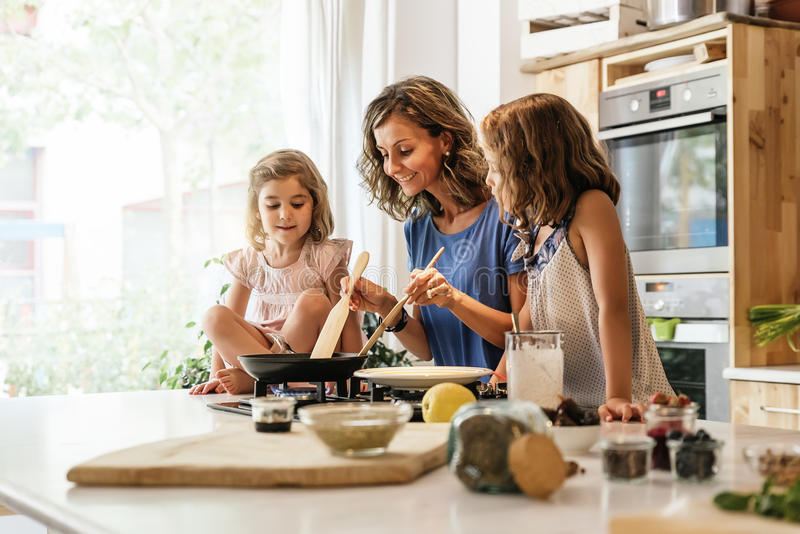Little sisters cooking with her mother in the kitchen. stock photography