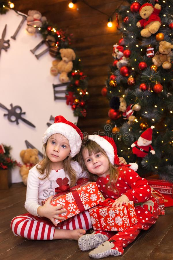 Little sisters girls in red pajamas decorate Christmas tree and open gifts in living room. Family with kids celebrating christmas stock photography