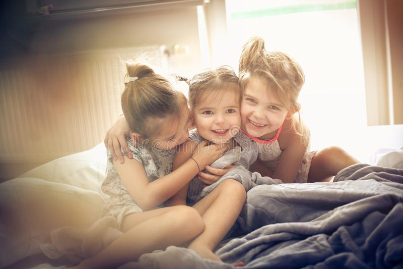 Little Sisters hug. Three little girls plying in bed. Space for copy stock photography