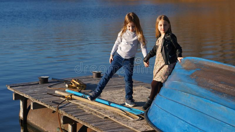 Little sisters on the pier. Charming children schoolgirls spending time by lake. Two kids playing on wooden pier. Fall weekend in open air. Leisure activity stock photos