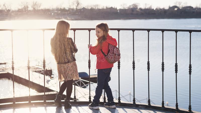 Little sisters on the pier. Two young schoolgirls are having confidential conversation. They stand on observation deck and see wooden pier. Sunny evening. Urban royalty free stock image