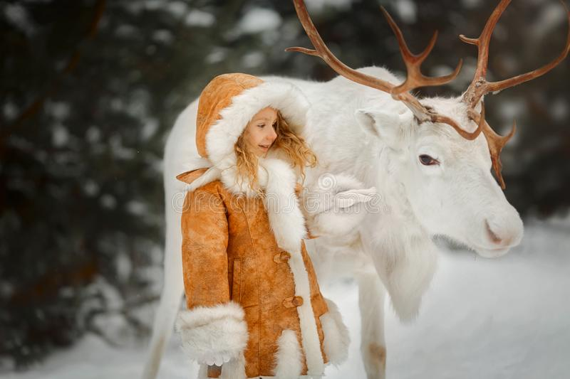 Portrait of beautiful Little girl in fur coat at winter forest stock image