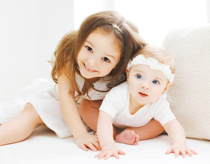 Little sisters together, children playing in white room stock image