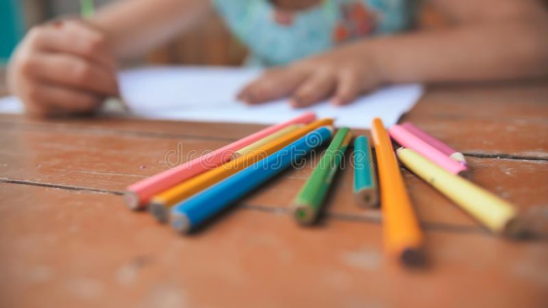 Little six-year-old girl draws with colored pencils. Close-up view of pencils. stock images