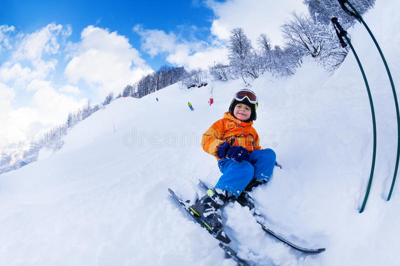 Little skier boy sit with ski in snow resting. Little boy sit in snow resting after skiing lessons royalty free stock images