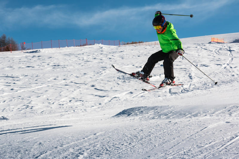 Little skier performs jump in the snow stock photos