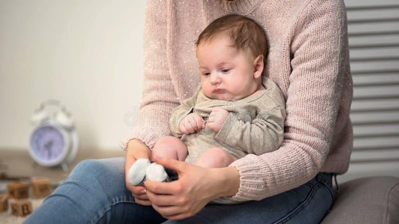 Little sleepy infant boy sitting on mothers lap, child care, loving family royalty free stock image