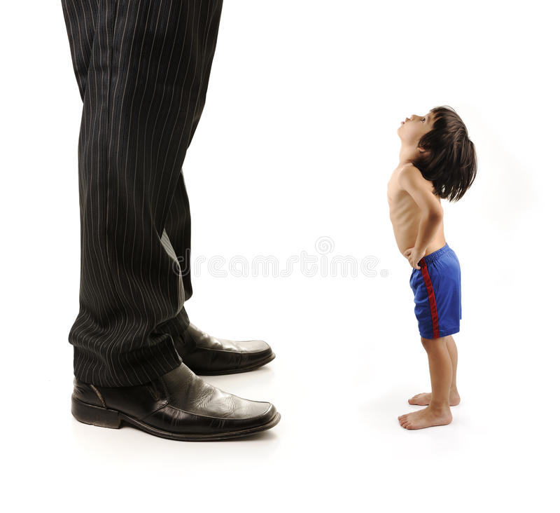 Little small child is looking at the giant legs. Of businessman adult royalty free stock image