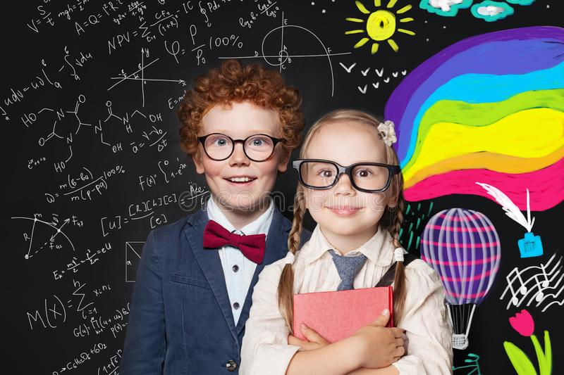 Little smart boy and girl on blackboard background with science formulas and arts pattern. Back to school concept stock images