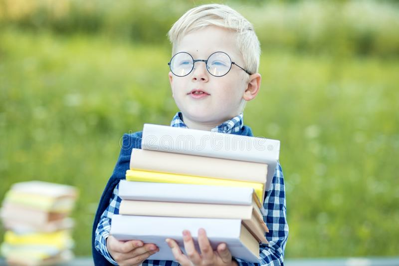 A little smart child holds a lot of textbooks in his hands. The concept of learning, school, mind, lifestyle and success stock photography