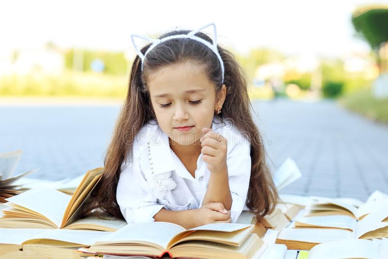 Little smart girl studying textbooks. The concept is back to school, education, reading, hobbies stock photos