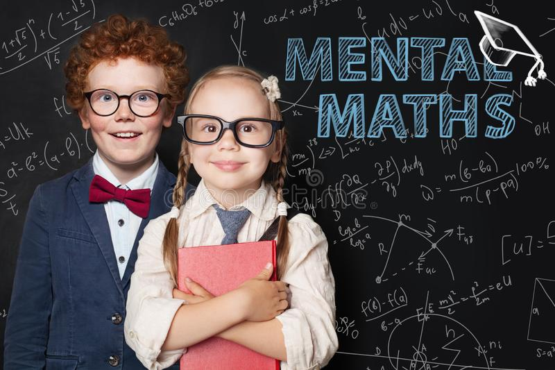 Little smart kids boy and girl student on blackboard background with science and maths formulas. Mental maths concept royalty free stock photo