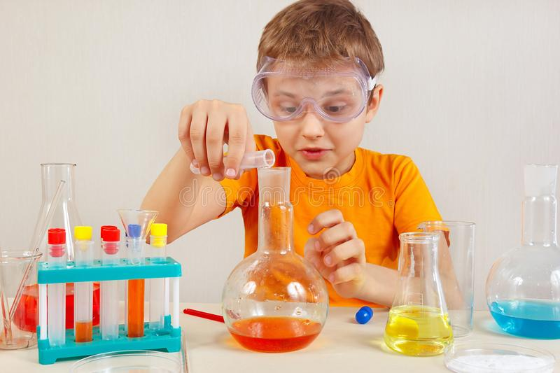 Little smart scientist in safety glasses doing chemical experiments in laboratory. Little smart scientist in safety glasses doing chemical experiments in the royalty free stock photography