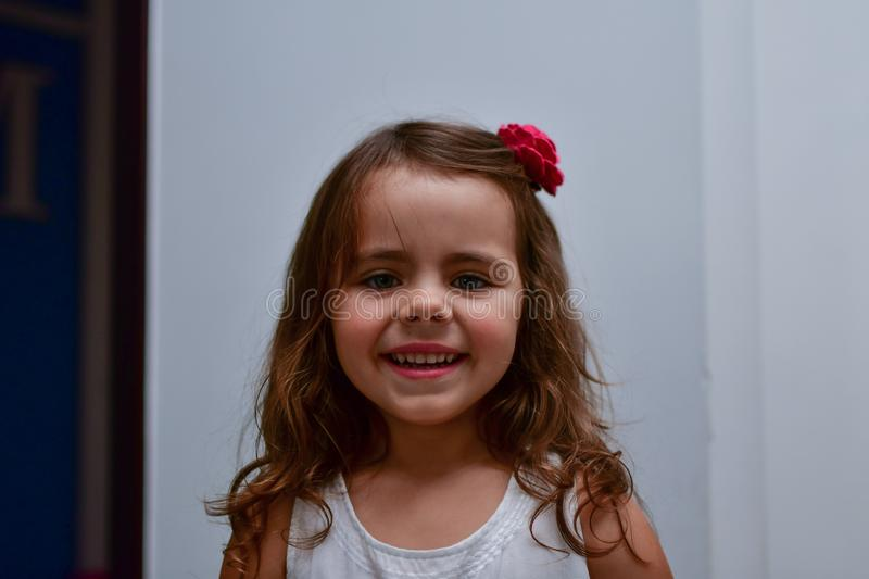 The little smiles girl with a flower in her hair royalty free stock photo