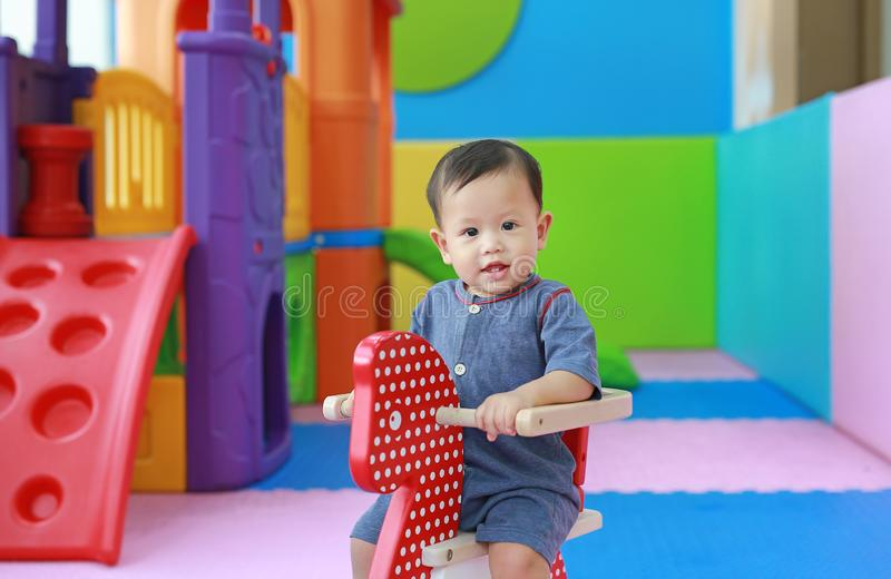Little smiling baby boy playing horse on playground, wooden rocking stock images