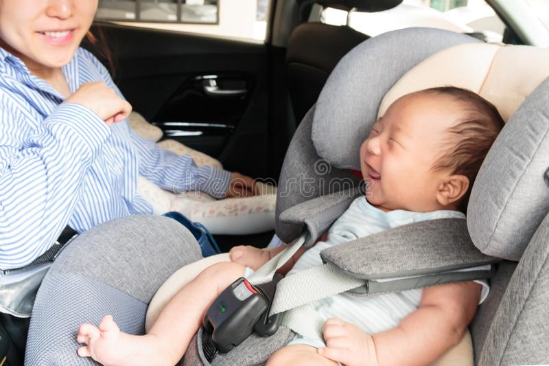 Asian little smiling baby child fastened with security belt in safety car seat stock image