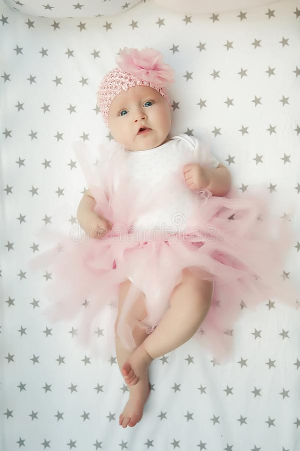 Little smiling baby girl sweet ballerina with fluffy pink skirt and flower in the cradle. Happy childhood. top view stock images