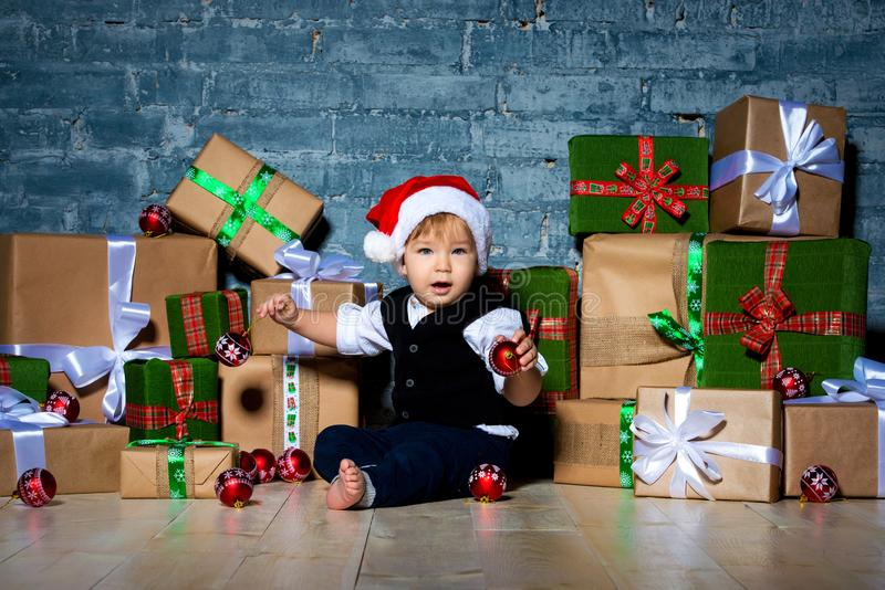 Little smiling baby santa claus in christmas hat and business suit . Happy new year and merry christmas. Holidays and gifts for royalty free stock images