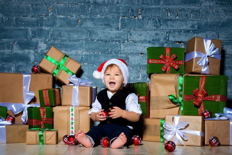 Little smiling baby santa claus in christmas hat and business suit . Happy new year and merry christmas. Holidays and gifts for royalty free stock photography