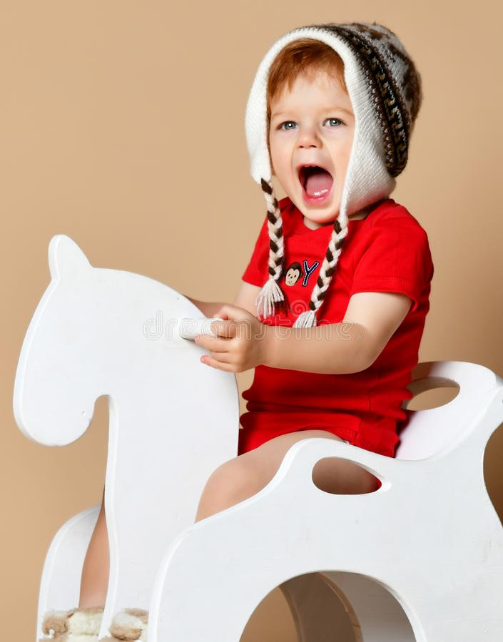 Little smiling baby sitting on a white horse, wooden rocking royalty free stock photography