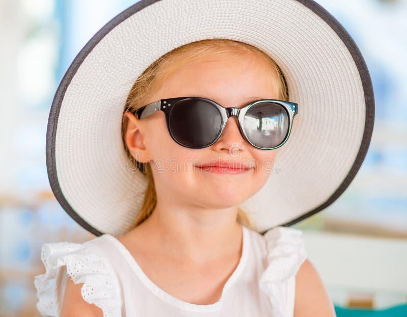 Little smiling blond girl in black sunglasses stock image