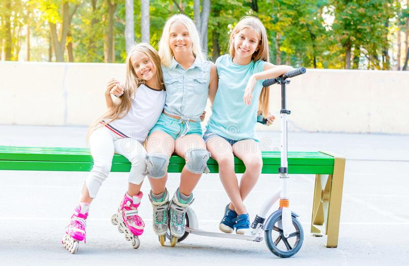Little smiling girls sitting on the green bench royalty free stock photography