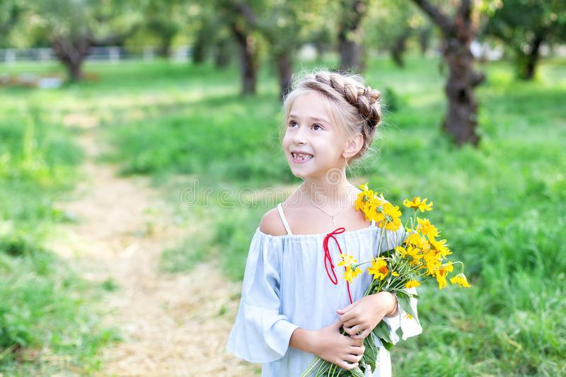 Little smiling blonde girl with a bouquet of yellow flowers on a background of the garden. A child in the autumn garden. Autumn fl stock image