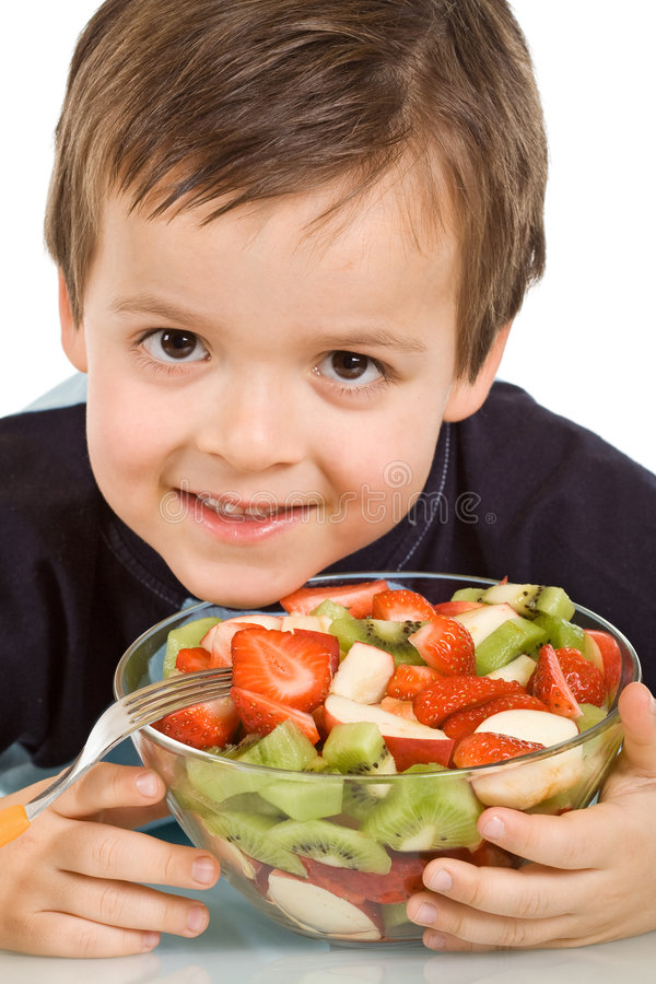 Little smiling boy with a bowl of sliced fruits stock photos
