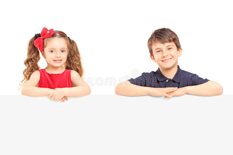Little smiling boy and girl standing behind a blank panel. Isolated on white background stock images