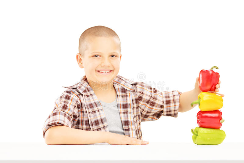 Download Little Smiling Boy Holding Colorful Peppers On A Table Stock Photo - Image of joyful, seasonal: 33514410